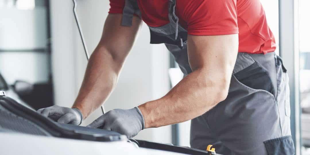 Automehaničar u radnji i radnom odjelu popravlja automobil