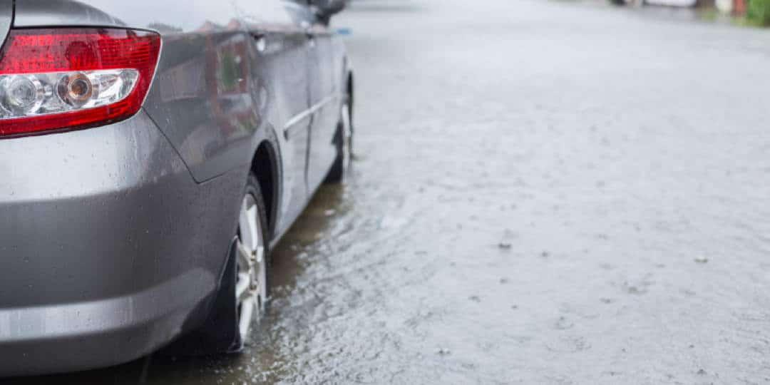 Automobil parkiran na ulici u velikoj lokvi vode dok kiši