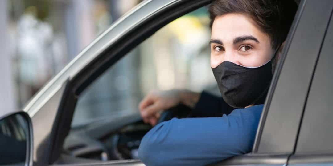 Muškarac u automobilu koji nosi masku