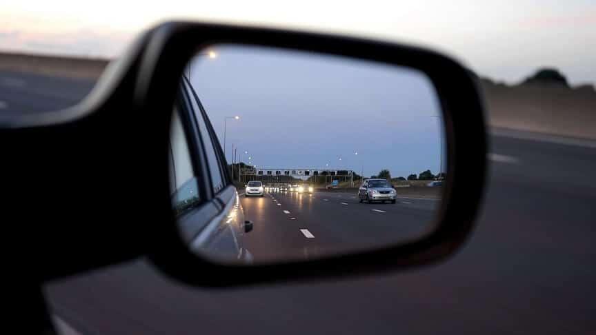 Retrovizor automobila u kojem se vide vozila na cesti iza automobila