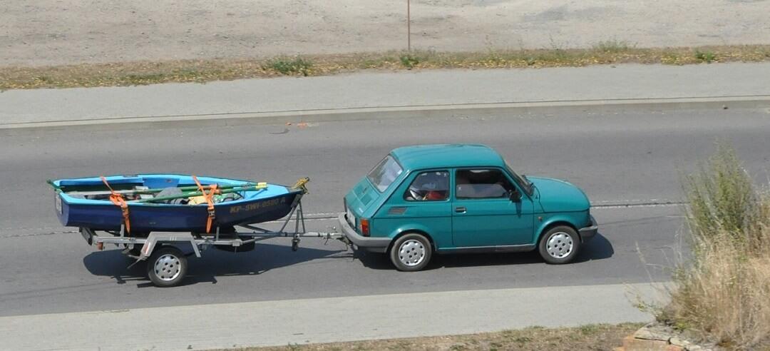 Zeleni automobil cestom vuče prikolicu na kojoj je čamac
