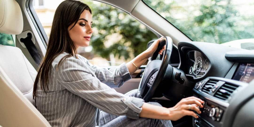 Nasmiješena vozačica automobila namješta glasnoću radija za vrijeme vožnje